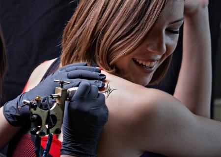 Girl tattoo artist works on the client Standard-Bild