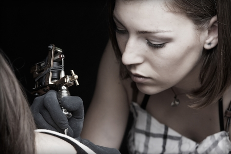 Girl tattoo artist works on the client Stock Photo