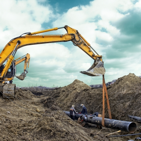 Construction site, excavator wearing metal pipe Stock Photo