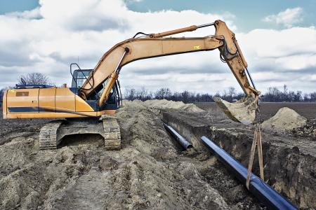 Obra de construcción, excavadora de metal usando tubería Foto de archivo