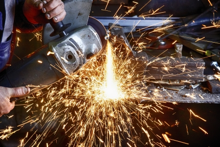 Heavy industry worker cutting steel plate with grinder in workshop. photo