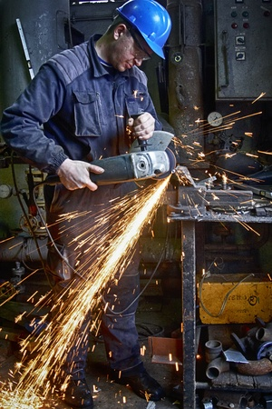 Heavy industry worker cutting steel plate with grinder in workshop.