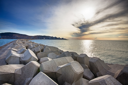 Breakwater with concrete blocks for protection of coast, sunset photo