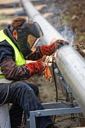 Soudeur de porter des vêtements de protection pour le soudage huile industrielle de construction et de gaz ou d'eau et une canalisation de plomberie d'assainissement à l'extérieur sur le site Banque d'images