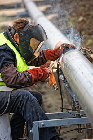 Welder wearing protective clothing for welding industrial construction oil and gas or water and sewerage plumbing pipeline outside on site