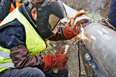 trabajador petroleros: Soldador uso de ropa protectora para la soldadura de aceite industrial de la construcci�n y el gas o el agua y la tuber�a de fontaner�a alcantarillado fuera de sitio