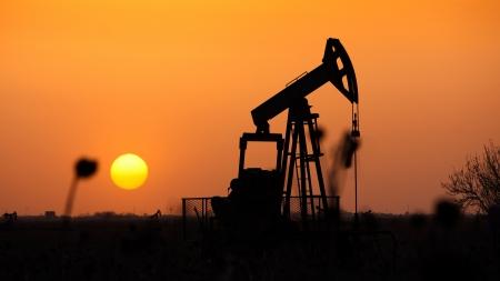 Pompe à huile, machine industrielle de pétrole dans le fond le coucher du soleil Banque d'images