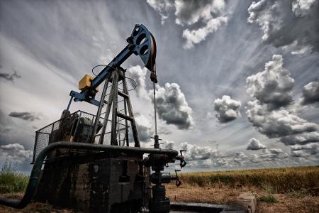 Pompe à huile, machine industrielle de pétrole dans le fond le coucher du soleil Banque d'images - 19455792