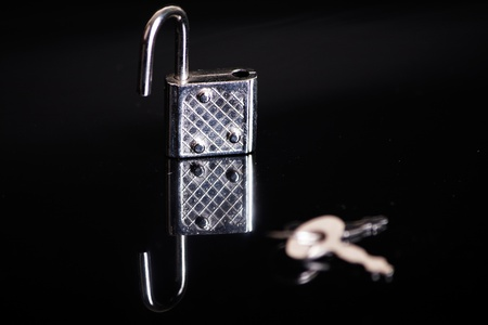 Small padlock with key on a black background, focus on the padlock photo