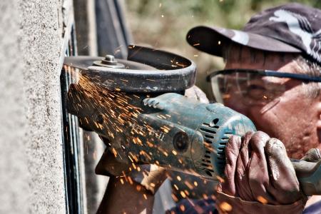 molinillo: hombre de corte de malla de metal con fresas Foto de archivo