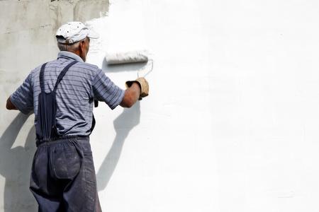 ouvrier de constructeur peinture façade de gratte-ciel avec rouleau Banque d'images