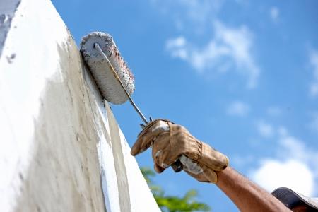 bouwer werknemer schilderij gevel van hoogbouw gebouw met roller Stockfoto