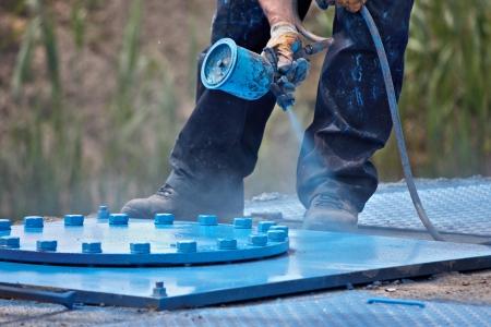 un travailleur pulvérisation de la peinture au pistolet de pulvérisation Banque d'images