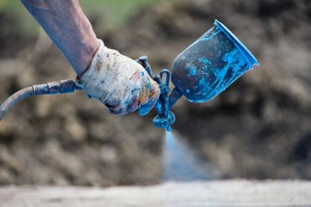 gun: a worker spraying the paint with the spray gun