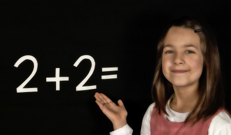 solves: Happy schoolgirl solves the task of the board Stock Photo