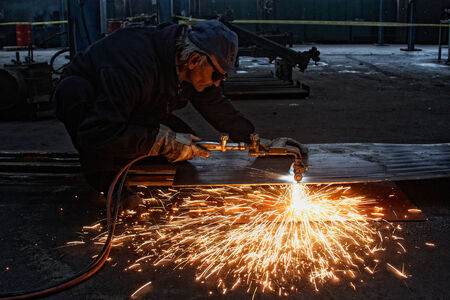 metal cutting with acetylene torch, focus on tools, low Light