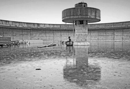 settling: Huge concrete circular sedimentation tank Water settling, purification in the water station  Man sitting under the pillar  As an umbrella