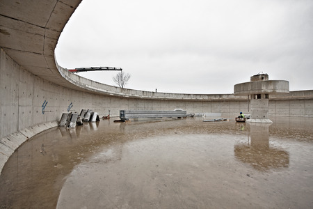 settling: Huge concrete circular sedimentation tank Water settling, purification in the water station. Man sitting under the pillar. As an umbrella Stock Photo