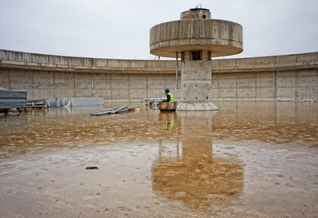 sludge: Huge concrete circular sedimentation tank Water settling, purification in the water station. Man sitting under the pillar. As an umbrella Stock Photo