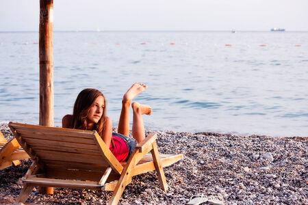 loungers: girl on the sun loungers on the beach