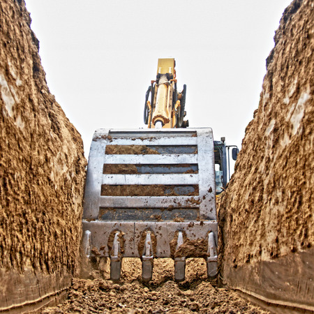 Excavator digging a deep trench on the site, focus forward Stock Photo