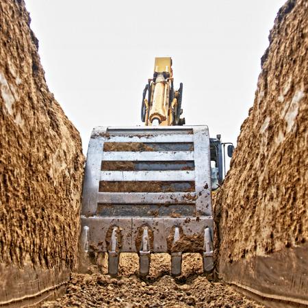 Pelle à creuser une tranchée profonde sur le site, se concentrer avant