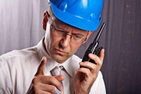 Un ingénieur avec un casque sur un chantier de construction communique Banque d'images