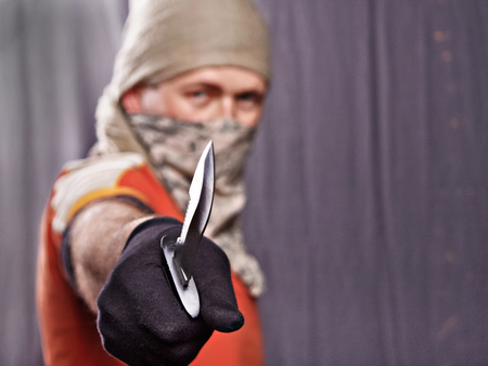murdering: masked man holding a knife on a black background, focus forward Stock Photo