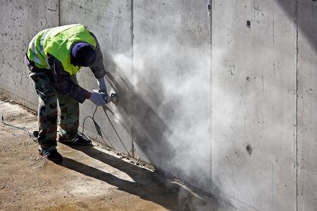 Travailleur broie mur de béton sur le site