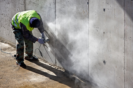 Worker grinds concrete wall on the site Stock Photo