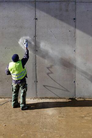 Hormigón: Trabajador muele muro de concreto en el sitio Foto de archivo