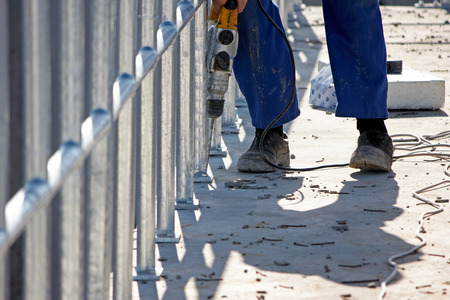 making hole: Worker drills holes in the concrete at the site