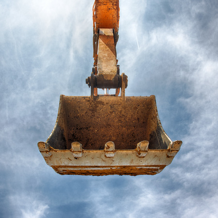 Excavator bucket on blue sky, Industrial excavator machine