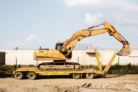 tracked: commercial delivery cargo truck with tracked excavator, focus on excavator