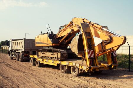 transport truck: commercial delivery cargo truck with tracked excavator, focus on excavator