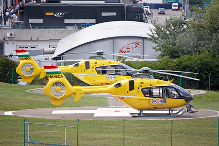 BUDAPEST, HUNGARY - JULY 26, 2014: Yellow helicopter Eurocopter AS-355N Ecureuil 2 on the runway above the Hungaroring Formula One Race Track.