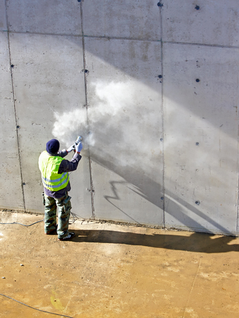 Builder worker with grinder machine cutting finishing concrete wall at construction site