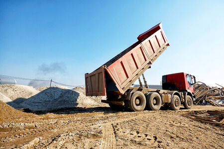 Dumper truck unloading soil or sand at construction site at blue sky background Stock Photo