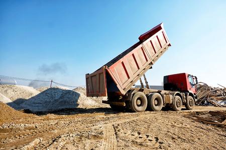 Dumper truck unloading soil or sand at construction site at blue sky background Standard-Bild