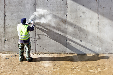 worker working: Builder worker with grinder machine cutting finishing concrete wall at construction site