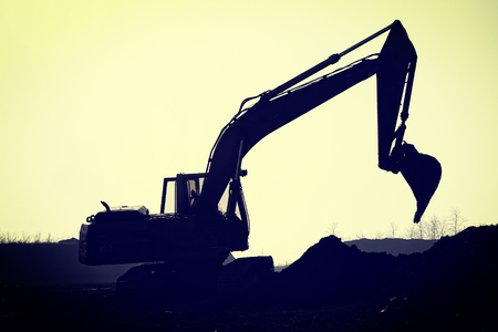 construction vehicle: Silhouette excavator on construction site