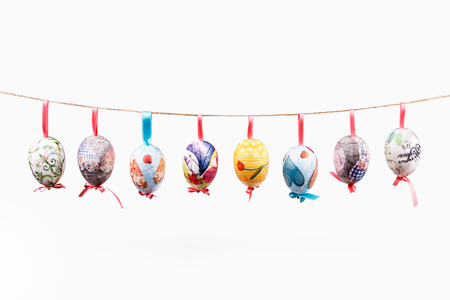 white eggs: Pretty Colored Easter Eggs hanging on wire isolated on white Stock Photo