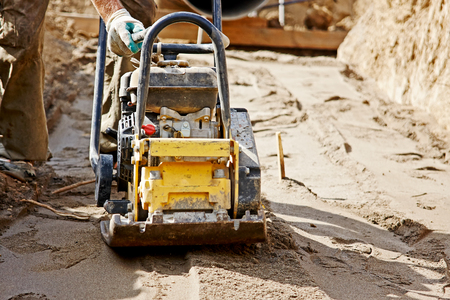 Worker use vibratory plate compactor to compacting ground at road repair Stock Photo