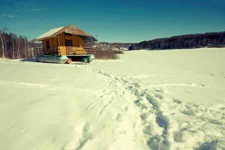 Wooden cottage in winter on the Vlasina lake