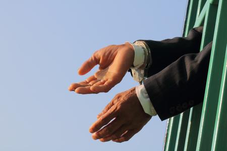 incarceration: Man behind jail bars reaching out