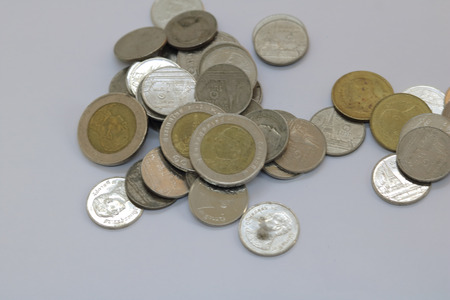 High resolution aerial shot of ten baht coins isolated on white background. Ten baht coins has silver and gold color in one coin