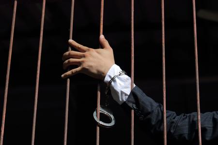 closeup on hands of man sitting in jail. Man behind jail bars on black background reaching Reklamní fotografie