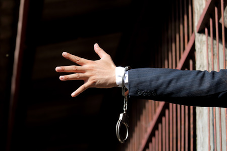 Abstract. Hands of the prisoner on a steel lattice close up. Prison, man in handcuffs.