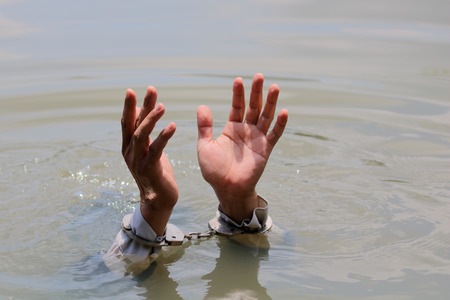 businessman was arrested by handcuffs and drowning in water with copyspace. Reklamní fotografie