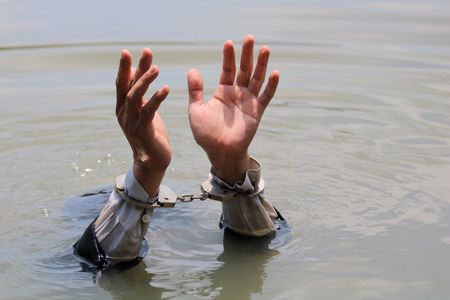 businessman was arrested by handcuffs and drowning in water with copyspace. Stock Photo